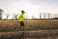 Man wearing VR glasses running in rural landscape - UUF10211