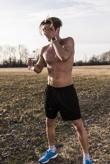 Barechested athlete in rural landscape pouring water over his face - UUF10214