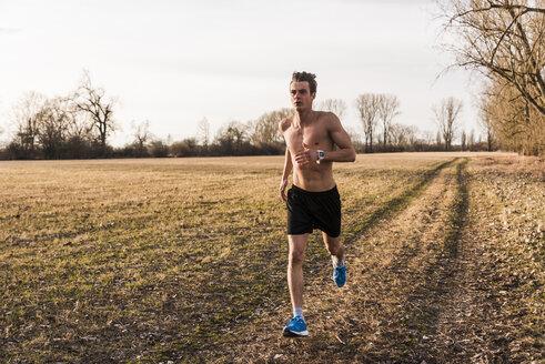 Barechested man running in rural landscape - UUF10217