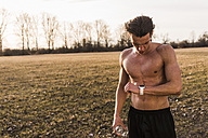 Barechested athlete in rural landscape looking on smartwatch - UUF10220