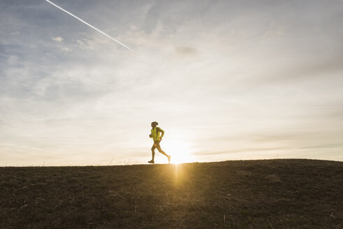 Man running in rural landscape at sunset - UUF10229