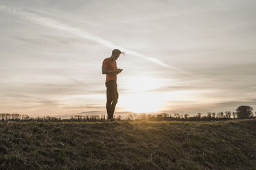 Athlete looking at cell phone in rural landscape at sunset - UUF10232