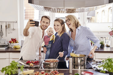 Happy family cooking in kitchen taking a selfie - FMKF03587