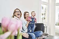 Happy grandmother, mother and baby girl at home - FMKF03593