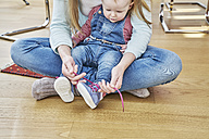 Mother and baby girl sitting on floor tying shoes - FMKF03596