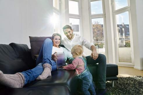 Parents with baby girl using laptop on couch - FMKF03599
