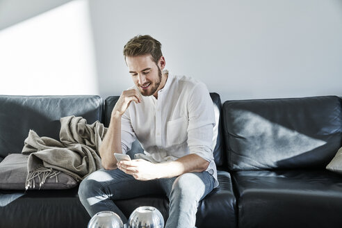 Smiling man sitting on couch looking at cell phone - FMKF03605