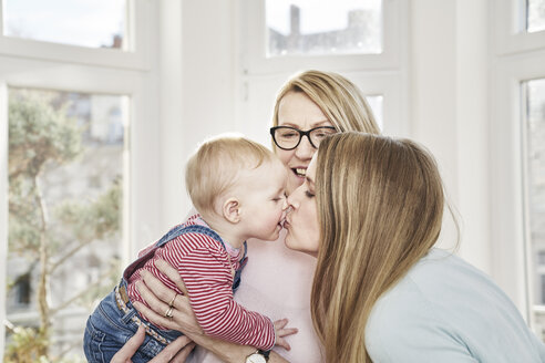 Baby girl being held by grandmother kissing mother - FMKF03608