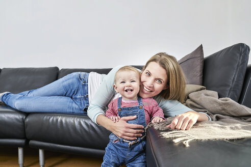Happy mother and baby girl at home on couch - FMKF03617