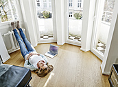 Woman at home lying on the floor next to laptop - FMKF03626