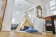 Woman lying in a teepee on the floor - FMKF03635