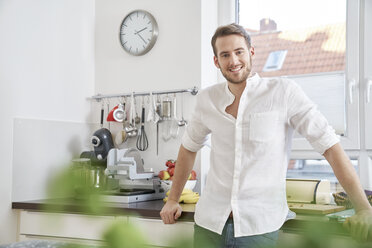 Portrait of smiling young man in kitchen - FMKF03641