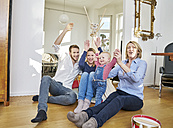 Happy familiy with baby girl playing in living room - FMKF03650
