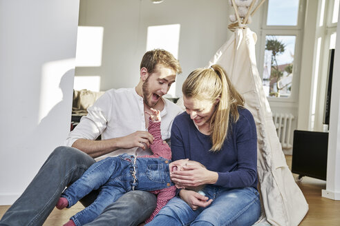 Happy family with baby girl playing at home - FMKF03653