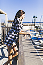 Young pretty woman wearing beach wear standing at balustrade at the harbour - GIOF02357