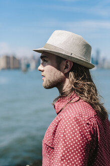 USA, New York City, man wearing hat at the waterfront with Manhattan skyline in background - GIOF02396