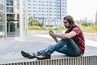 Man sitting on a wall with earbuds using cell phone - GIOF02405