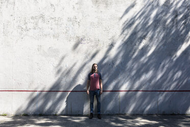 Man standing in front of concrete wall - GIOF02420