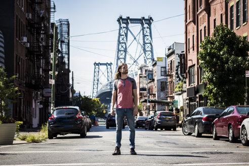 USA, New York City, man standing on the street looking around in Williamsburg, Brooklyn - GIOF02426