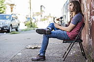 USA, New York City, man sitting on a chair using cell phone in Williamsburg, Brooklyn - GIOF02429