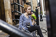 USA, New York City, woman sitting on stoop drinking a smoothie in Manhattan - GIOF02440