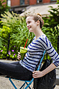 Smiling young woman having a break drinking a smoothie outdoors - GIOF02446