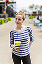 USA, New York City, confident woman drinking a smoothie in Manhattan - GIOF02449