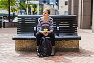 USA, New York City, woman sitting on a bench drinking a smoothie in Manhattan - GIOF02458