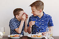 Two young boys eating tapas, laughing and making salami eyes - NMSF00011