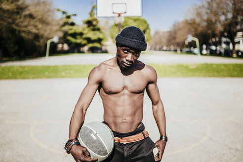 Portrait of barechested basketball player on court - GIOF02468