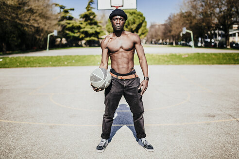 Portrait of barechested basketball player on court - GIOF02471