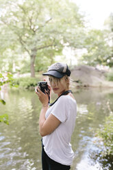 Young woman with a vintage camera taking pictures in park - BOYF00728
