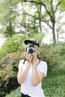 Young woman with a vintage camera taking pictures in park - BOYF00731