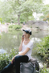 Young woman sitting at lakeside in park talking on cell phone - BOYF00737