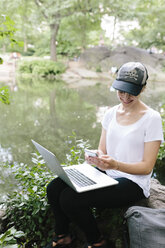 Young woman sitting at lakeside in park using cell phone and laptop - BOYF00746