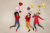 Female friends chatting and gossiping with emojies over their heads - BAEF01280