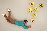 Man chatting on his smart phone, sending emojies - BAEF01292
