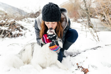 Young woman kissing her dog in the snow - MGOF03079