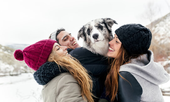 Three friends having fun with a dog in the snow - MGOF03085