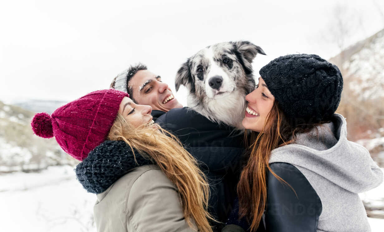 Three friends having fun with a dog in the snow - MGOF03085 - Marco Govel/Westend61