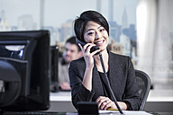 Smiling woman in office talking on phone - ZEF13163