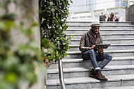 Man sitting on staircase using tablet - MAUF00999