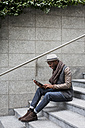 Man sitting on staircase using tablet - MAUF01002