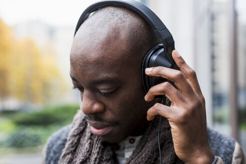Bald man listening music with headphones - MAUF01008