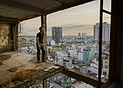 Vietnam, Ho Chi Minh City, man standing in ruin of a skyscraper - TOVF00069