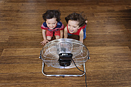 Twin brothers kneeling on wooden floor in front of fan having fun, top view - LITF00540