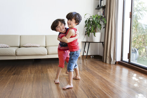 Twin brothers playfighting in the living room - LITF00543