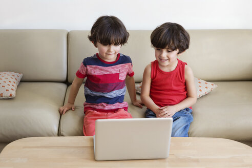 Twin brothers sitting side by side on the couch looking at laptop - LITF00546