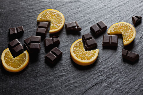 Cocolate pieces with orange slices on black slate - CSF28125