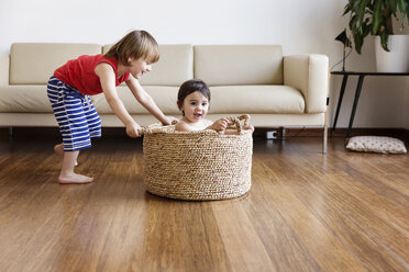 Toddler girl sitting in a basket while her brother pushing her around in the living room - LITF00563